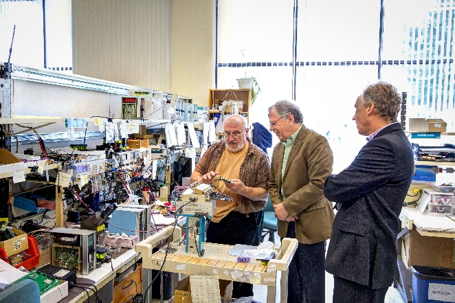 Three men standing at a work bench looking at a circuit board.
