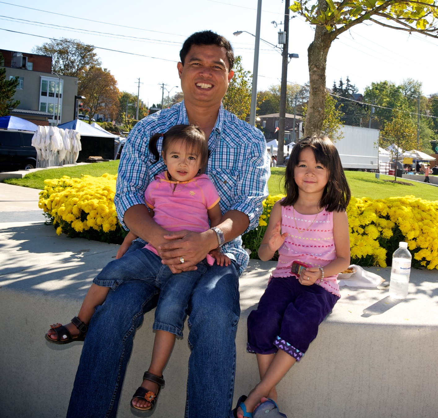 Father and two daughters sitting in Newmarket park