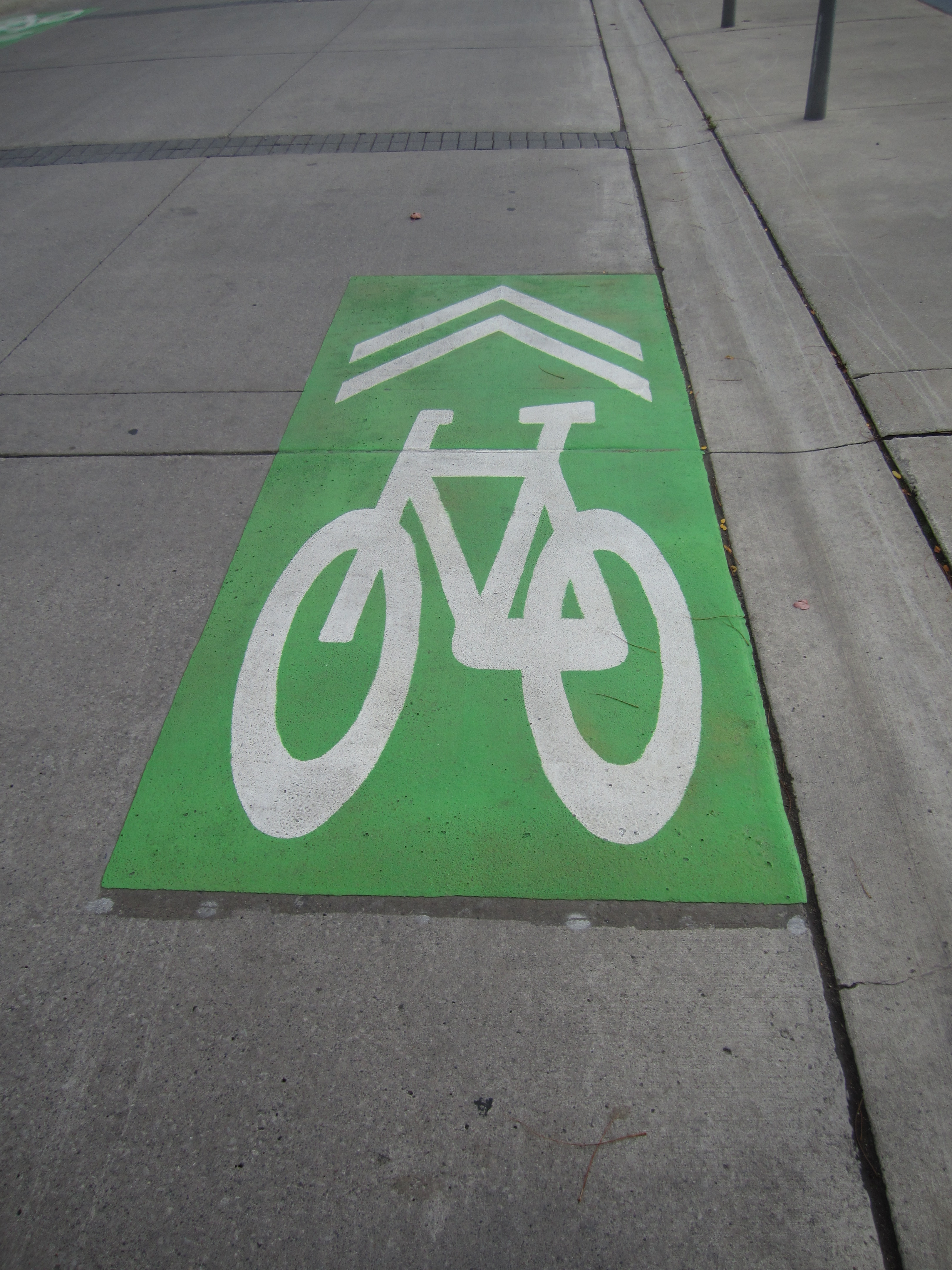 a picture of a white painted bike symbol with double arrows ontop of a green square background