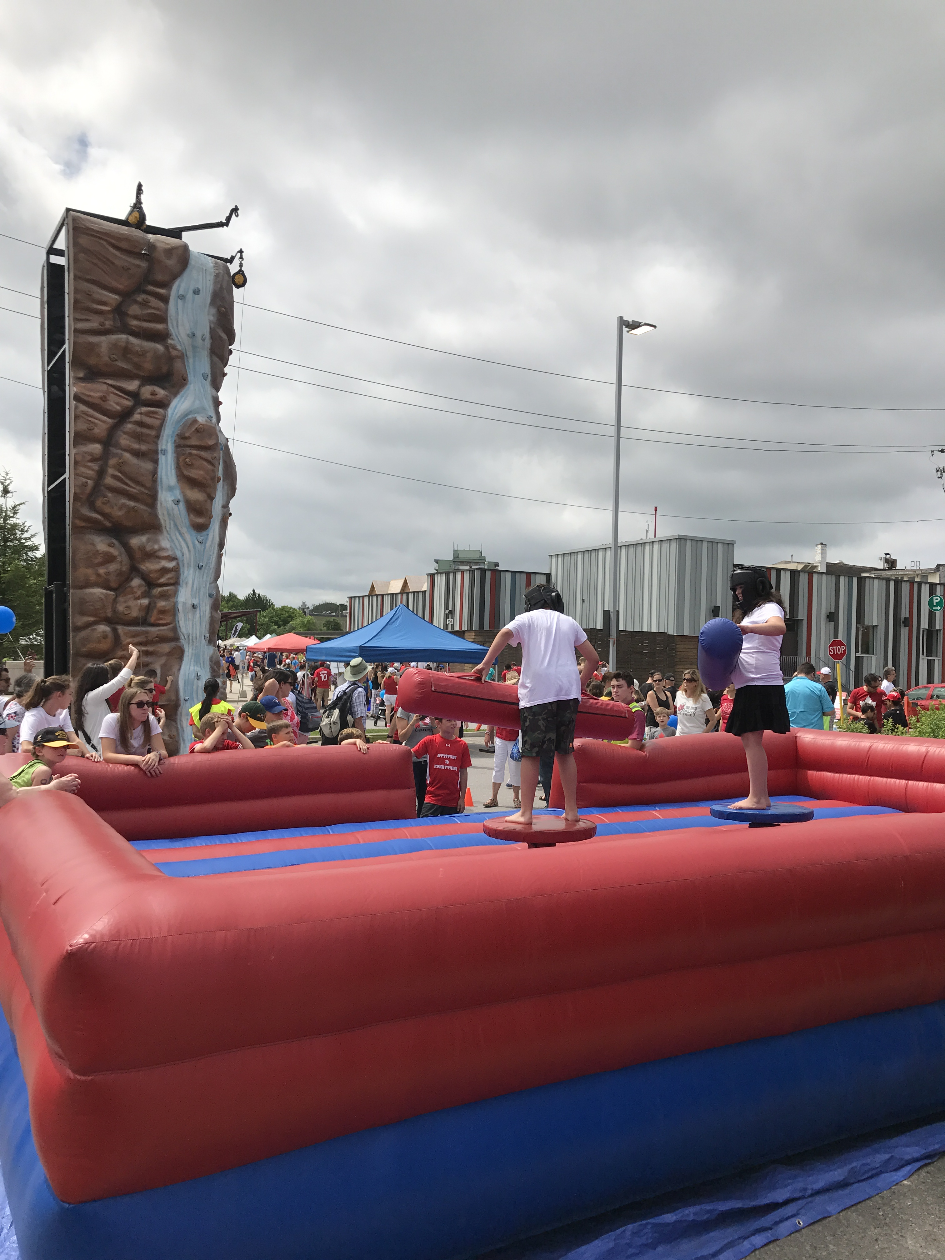 shot of patrons playing on the Canada 150 Inflateable Jousting & Rock CLimbing wall