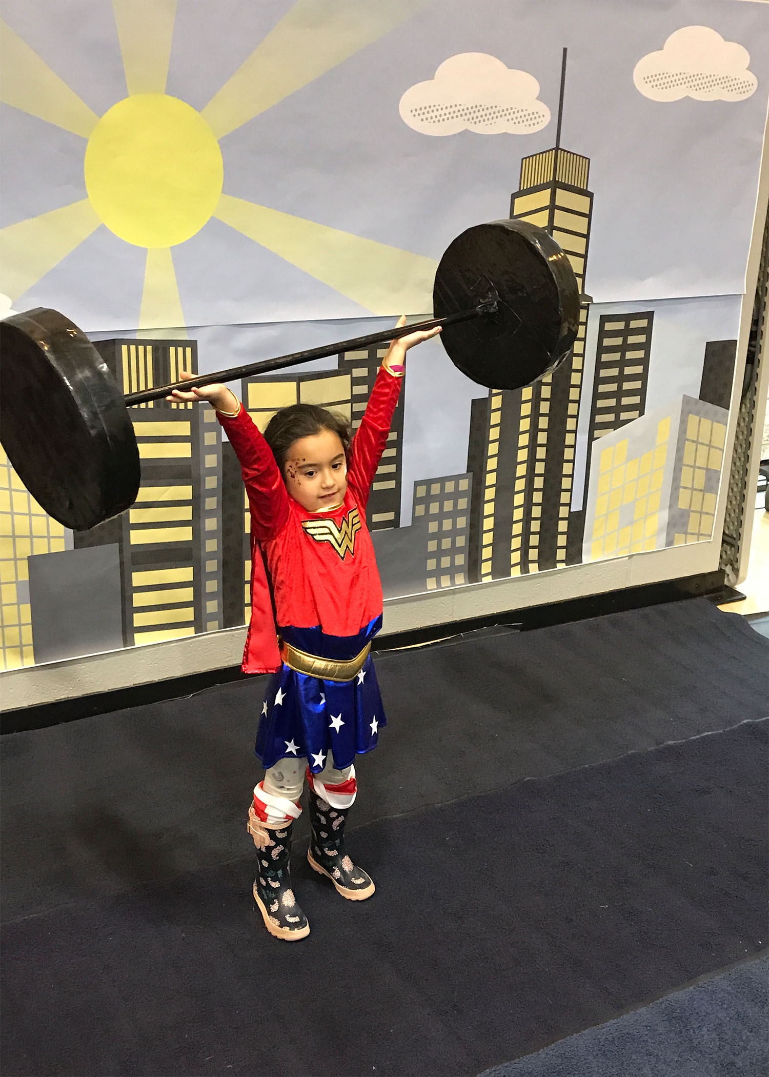 Young WonderGirl lifting weight high above her head
