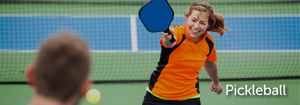 image of two people playing pickleball and smiling