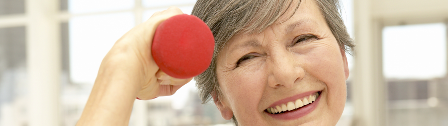 image of senior patron smiling and holding a red weight